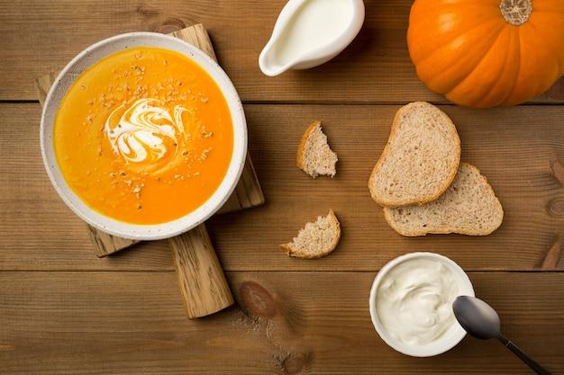 Domowa zupa dyniowa w białym talerzu ze śmietaną i chlebem na desce do krojenia płasko leżała na drewnianym tle