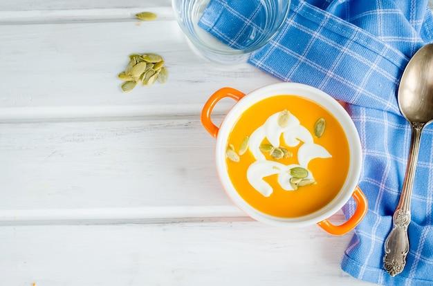 Domowa zupa dyniowa w ceramicznej misce z nasionami, śmietaną i grzankami chleba na tle