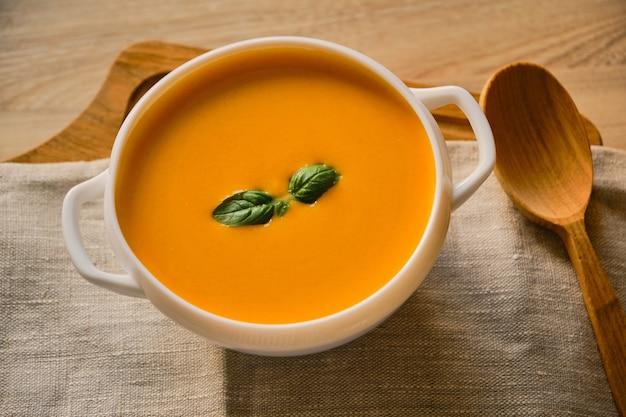 Domowa zupa dyniowa z bazylią w misce.