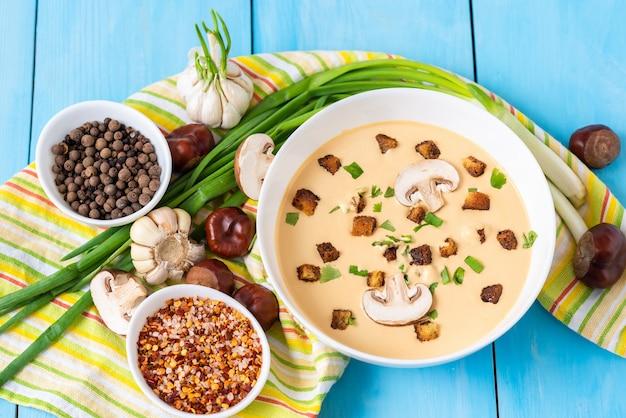 Domowa zupa kasztanowa na niebieskiej drewnianej powierzchni z różnymi przyprawami.