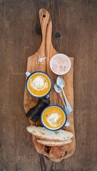 Domowa zupa krem dyniowy w emaliowanych kubkach z ziołami i kawałkami świeżego chleba na oliwkowej desce
