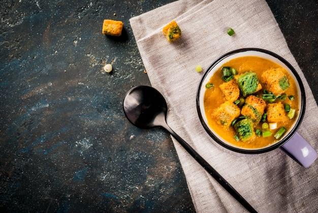 Domowa zupa krem z marchewki puree, z krakersami, świeżymi ziołami i śmietaną