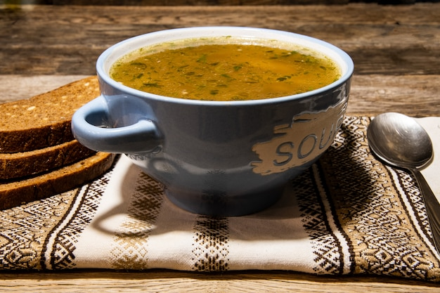 Domowa zupa mięsna w ceramicznej niebieskiej misce, metalowa łyżka, serwetka ludowa na drewnianym stole.