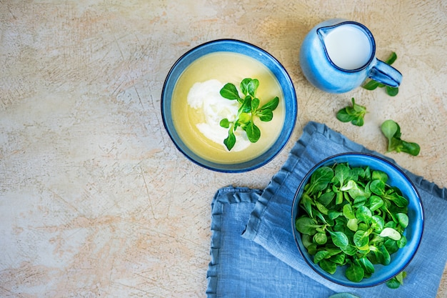 Domowa zupa przecierowa ze świeżej cukinii i szpinaku yang na jasnożółtym tle.