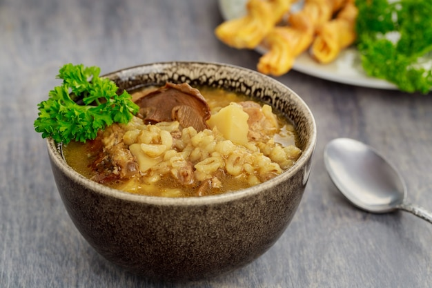 Domowa zupa z grzybami, kaszą jęczmienną i krakersami.