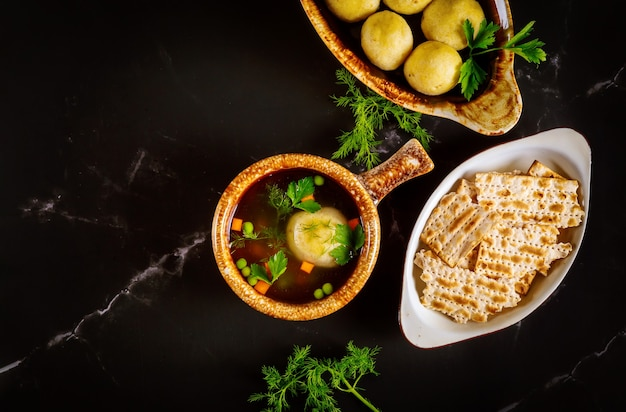 Domowa zupa z kulki macy na dwóch talerzach z łyżeczkami na czarnej powierzchni.