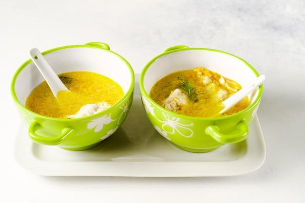 Domowa zupa z kurczaka z makaronem podawana w jasnozielonych miseczkach z ceramicznymi łyżkami