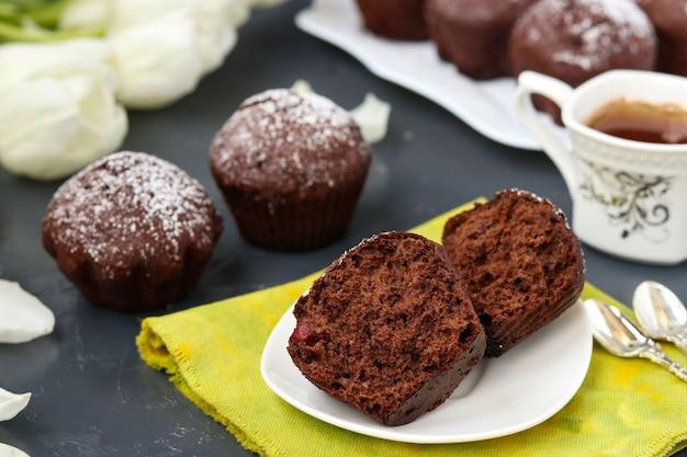 Domowe babeczki czekoladowe z wiśniami, pokryte cukrem pudrem umieszczonym na ciemno