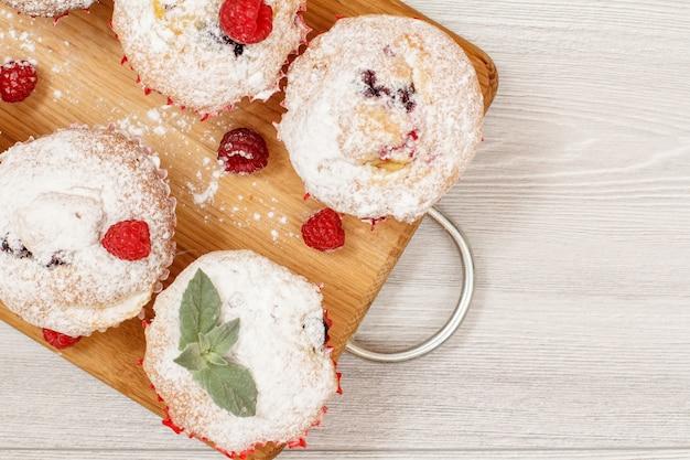Domowe babeczki owocowe posypane cukrem pudrem i świeżymi malinami na drewnianej desce do krojenia. świąteczne słodycze i wypieki. widok z góry z miejsca na kopię.