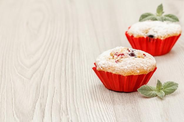 Domowe babeczki owocowe posypane cukrem pudrem i świeżymi malinami na drewnianym biurku. świąteczne słodycze i wypieki.