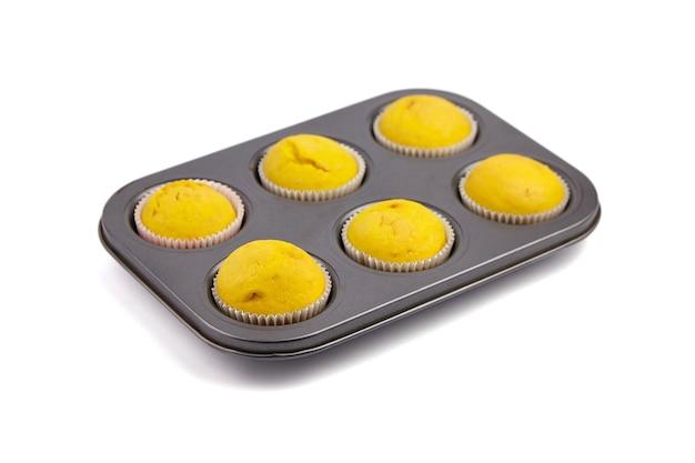 Domowe babeczki w nieprzywierającej blasze do pieczenia cupcake na białym tle