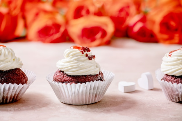 Domowe babeczki z czerwonego aksamitu z bitą śmietaną w rzędzie, biała serwetka ze wstążką, kwiaty róż, drewniane serca na różowym stole tekstury. deser walentynki.