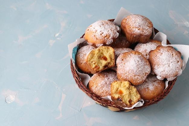 Domowe babeczki z suszonymi morelami, posypane cukrem pudrem w wiklinowym koszyczku na jasnoniebieskim tle