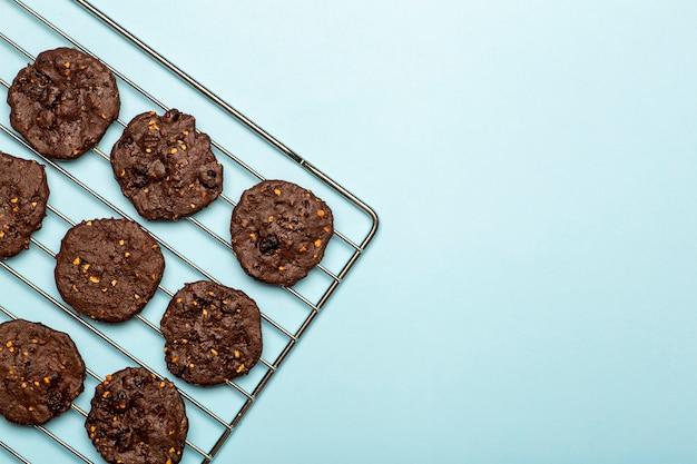 Domowe bezglutenowe ciasteczka z kawałkami czekolady ze zbożami, orzechami i ekologicznym kakao. ciastka i ciastka z mąki żytniej na kolorowym tle. koncepcja bezglutenowa
