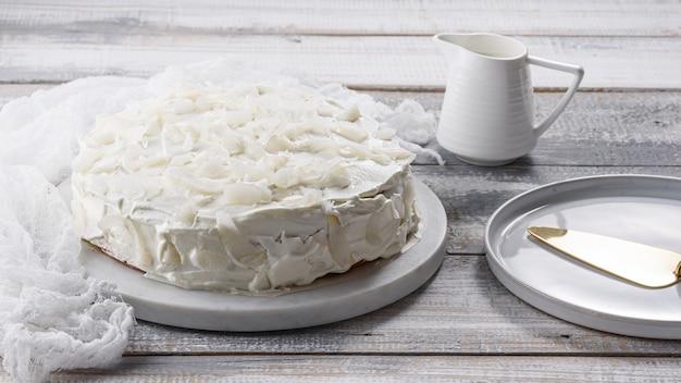 Domowe białe ciasto kokosowe na marmurowej desce na białym tle domowe gotowanie tort weselny