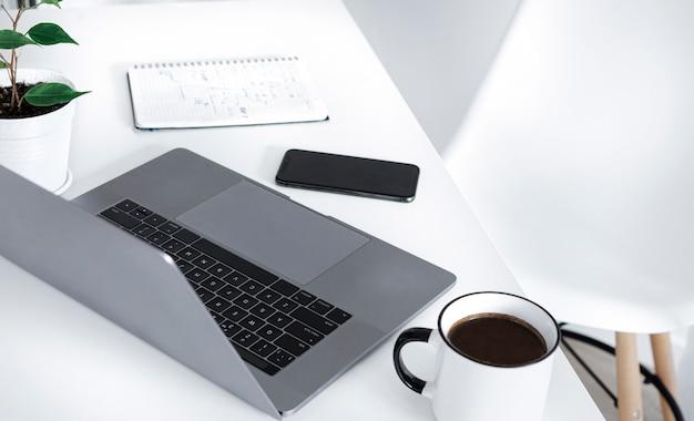 Domowe biuro z komputerem, notatnikiem, filiżanką kawy i smartfonem. koncepcja pracy zdalnej lub uczenia się online