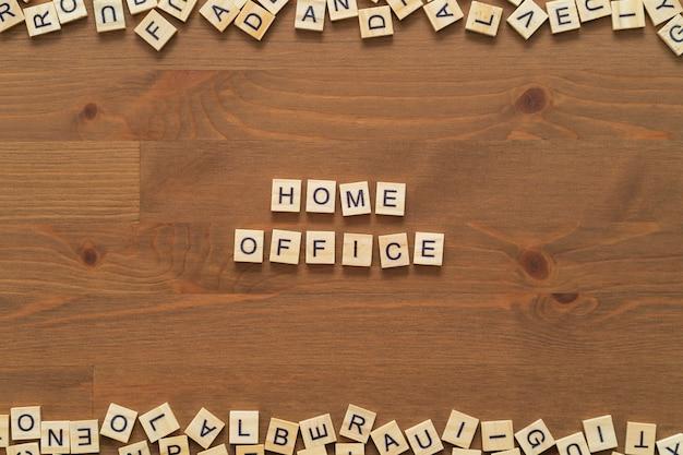 """""""domowe biuro"""" zawiera słowa napisane drewnianymi literami na drewnianym biurku."""