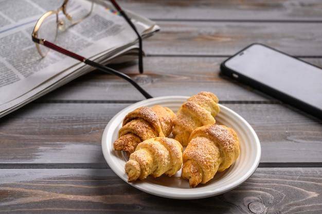 Domowe bułeczki z ciasteczkami na białym talerzu na drewnianej powierzchni w pobliżu gazety smartfona i okularów
