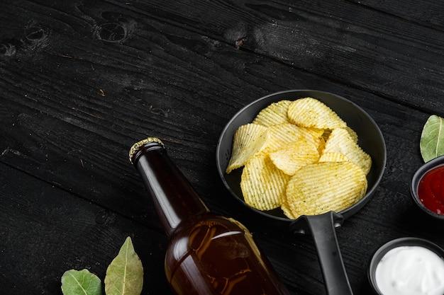 Domowe chipsy ziemniaczane i butelka piwa, na czarnym drewnianym tle, z miejscem na tekst