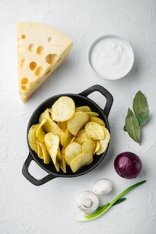 Domowe chipsy ziemniaczane zestaw z serem i cebulą, z sosami dip pomidorowymi z kwaśną śmietaną, na białej powierzchni kamienia, widok z góry na płasko