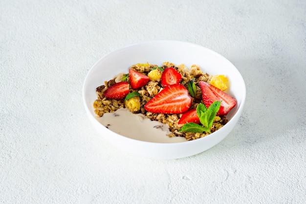 Domowe chrupiące muesli z orzechami, suszonymi owocami, świeżymi truskawkami, miętą i jogurtem (fermentowane mleko pieczone) na białym talerzu.