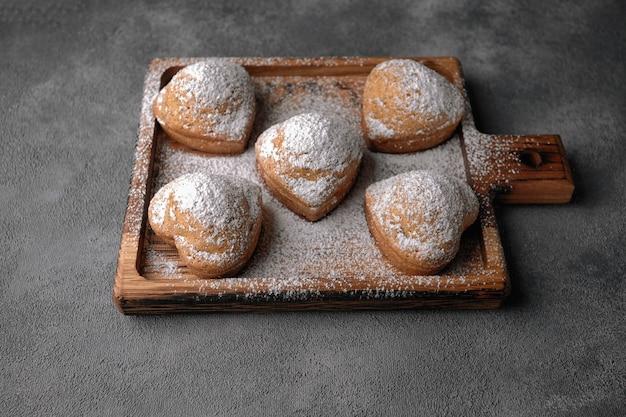 Domowe ciasta, babeczki z cukrem pudrem, na drewnianej desce, na szarym stole