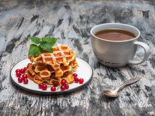 Domowe ciasta, gofry z czerwonymi owocami wiśni, herbata w szarym kubku