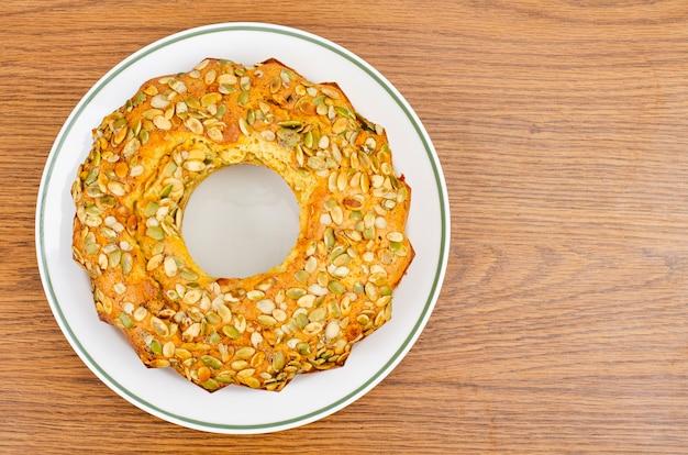 Domowe ciasta, muffinka z pestkami dyni na białym talerzu.