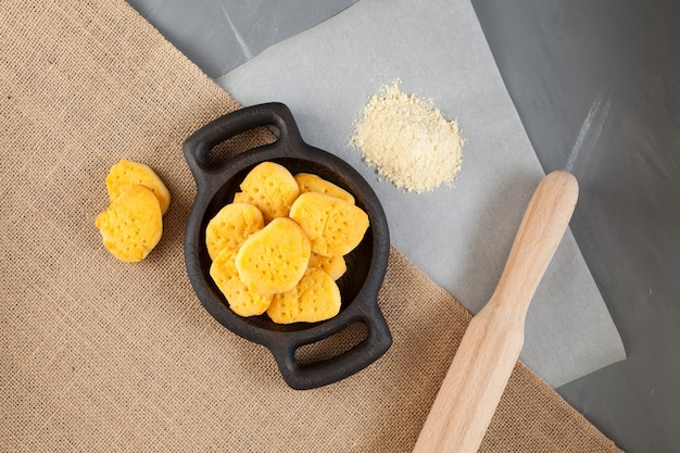 Domowe ciasteczka bezglutenowe. mąka na papierze do pieczenia i wałek do ciasta leżą na stole.