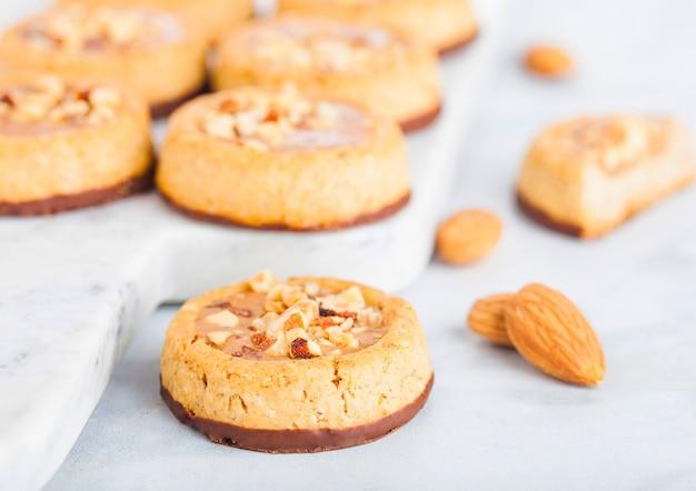 Domowe ciasteczka biszkoptowe z orzechami migdałów i masłem orzechowym na marmurowej desce na stole w kuchni.