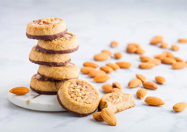 Domowe ciasteczka biszkoptowe z orzechami migdałów i masłem orzechowym na marmurowych podstawkach na stole w kuchni.