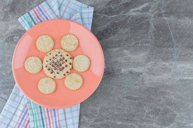Domowe ciasteczka na pomarańczowym talerzu na szarym tle.