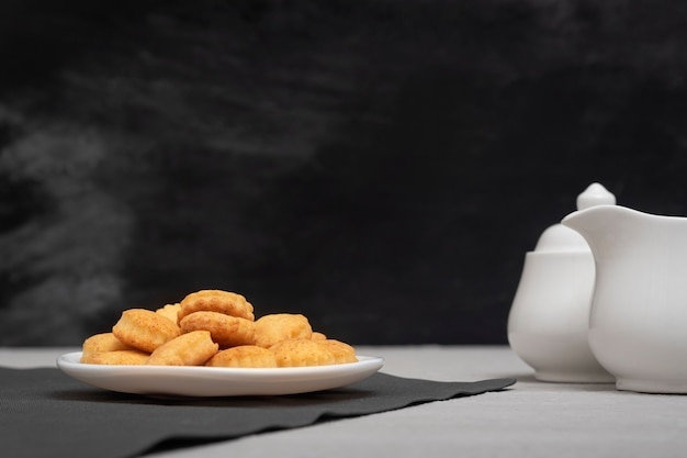 Domowe ciasteczka na talerzu. czarne tło, śmietanka i cukiernica. pieczenie na herbatę. pyszne śniadanie.