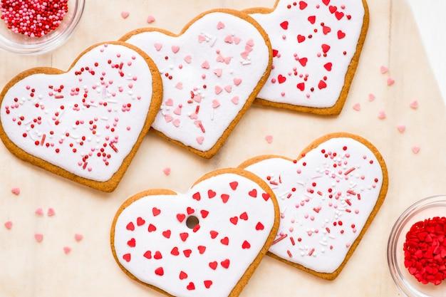 Domowe ciasteczka na walentynki posypane sercami na jasnym tle