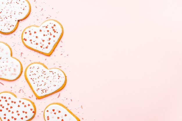 Domowe ciasteczka na walentynki posypane sercami na różowym tle
