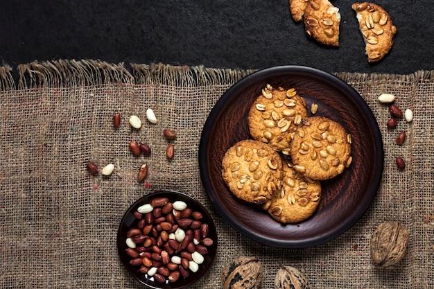 Domowe ciasteczka orzechowe na brązowym talerzu z surowymi orzeszkami ziemnymi