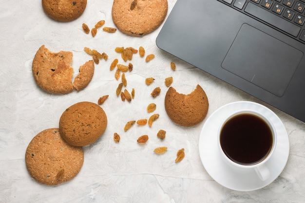Domowe ciasteczka owsiane, filiżanka kawy i laptop na jasnym kamieniu. dni studenckie