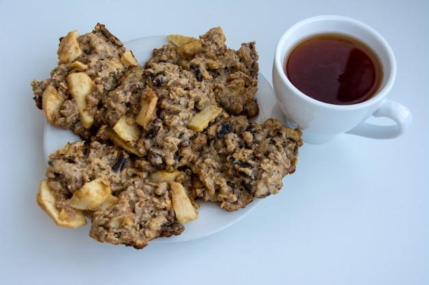 Domowe ciasteczka owsiane na talerzu z nakrętką herbaty na białym tle.