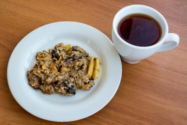 Domowe ciasteczka owsiane na talerzu z nakrętką herbaty na drewnianym stole.