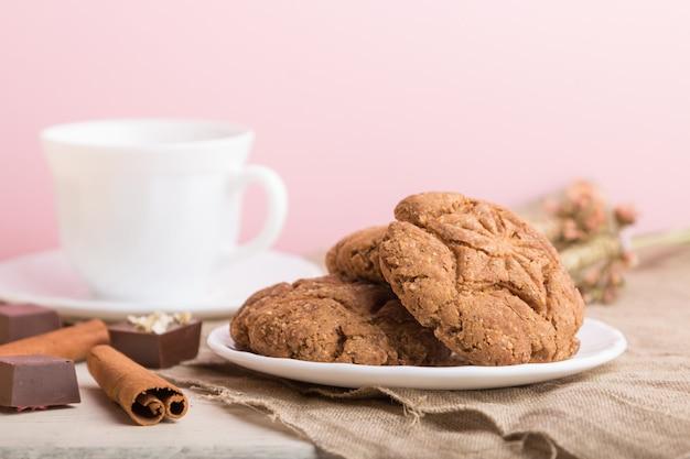 Domowe ciasteczka owsiane z filiżanką kakao na różowej pastelowej ścianie. widok z boku, selektywne focus.