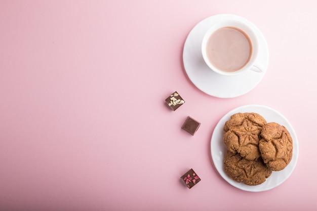 Domowe ciasteczka owsiane z filiżanką kakao na różowym pastelowym tle. widok z góry, kopia przestrzeń.