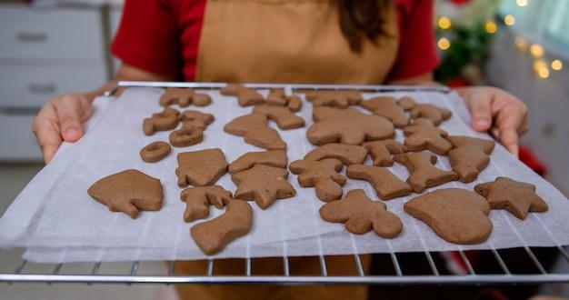 Domowe ciasteczka świąteczne na boże narodzenie i szczęśliwego nowego roku. kobieta gotowania piernika z przyjacielem i rodziną na ferie zimowe w domu.