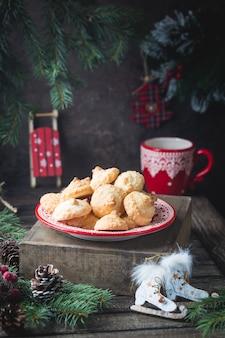 Domowe ciasteczka świąteczne w czerwonym talerzu ze świąteczną dekoracją