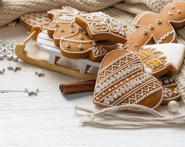 Domowe ciasteczka świąteczne z zabawkowymi saniami i beżowym szalikiem z wełny z dzianiny na białym drewnianym stole.