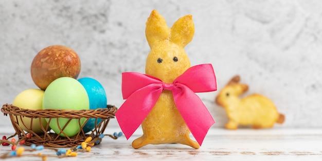 Domowe ciasteczka w kształcie królika z czerwoną kokardką i pisankami na świetle.