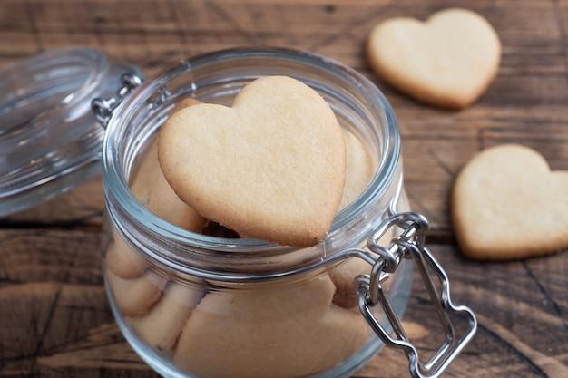 Domowe ciasteczka w kształcie serc w szklanym słoiku, drewniany stół.