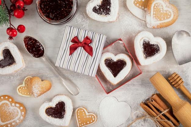 Domowe ciasteczka w kształcie serca z dżemem malinowym na białym drewnianym stole na boże narodzenie lub walentynki.