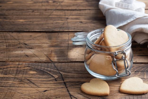 Domowe ciasteczka w kształcie serduszek w słoiku na drewnianym tle.
