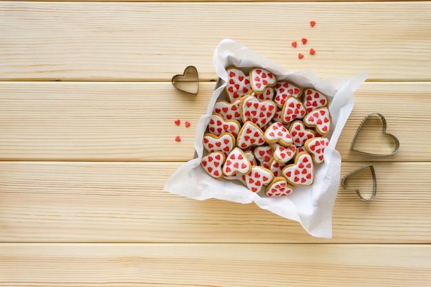 Domowe ciasteczka w kształcie serduszek z lukrem i posypką w pudełku na podłoże drewniane.