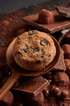Domowe ciasteczka z kawałkami czekolady na drewnianej łyżce z proszkiem kakaowym i cukierkami